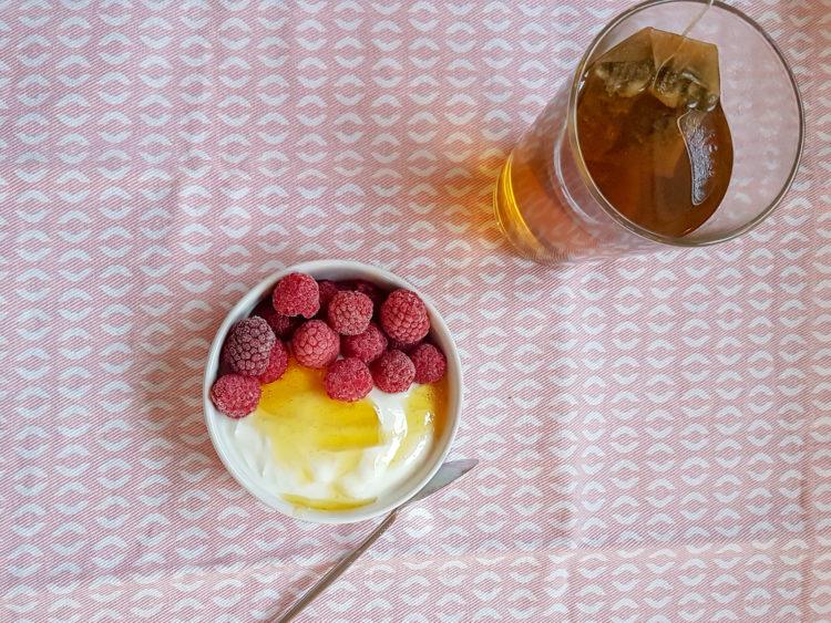 petit bol de fromage blanc recouvert de framboises et miel avec un verre de thé