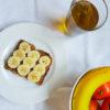 assiette contenant une tartine de morceaux de banane sur une couche de pâte à tartiner à l'amande avec un bol rempli de fruit et un verre de thé