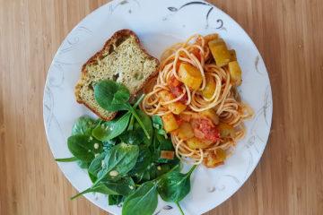 assiette composée de cake à la courgette et au pesto, de pousses d'épinard et de pâte à la sauce tomate
