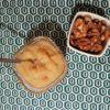 Compote de pomme et de banane dans une coupelle en verre accompagnée de cerneaux de noix