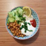 Grand bol contenant du riz avec des pois chiches, du concombre une sauce au fromage blanc et chili et une rondelle de citron