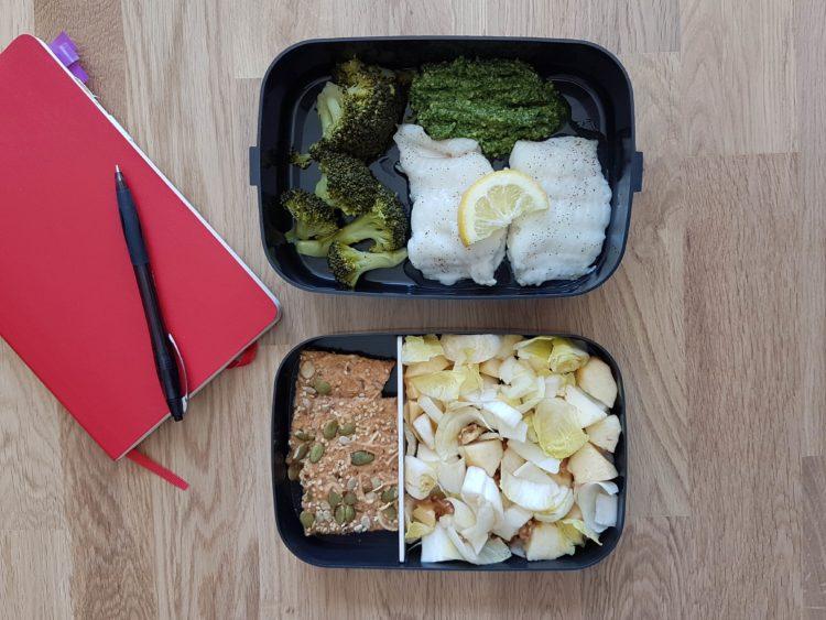 Lunchbox avec une partie contenant la salade aux endives et aux pommes et une autre partie contenant le filet de bar brocoli et pesto carnet rouge et stylo