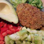 Galettes végétales présentées dans une assiette avec du poivron rouge du concombre de l'avocat et une salade verte