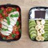 Linchbox présentant un compartiment avec des pâtes à la sauce tomate et un filet de poulet coupé et un autre compartiment avec du kiwi de la banane coupés et deux carrés de chocolat