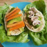 2 tartines végétales avec houmous et crudités présentées sur des feuilles de salade dans une assiette bleue