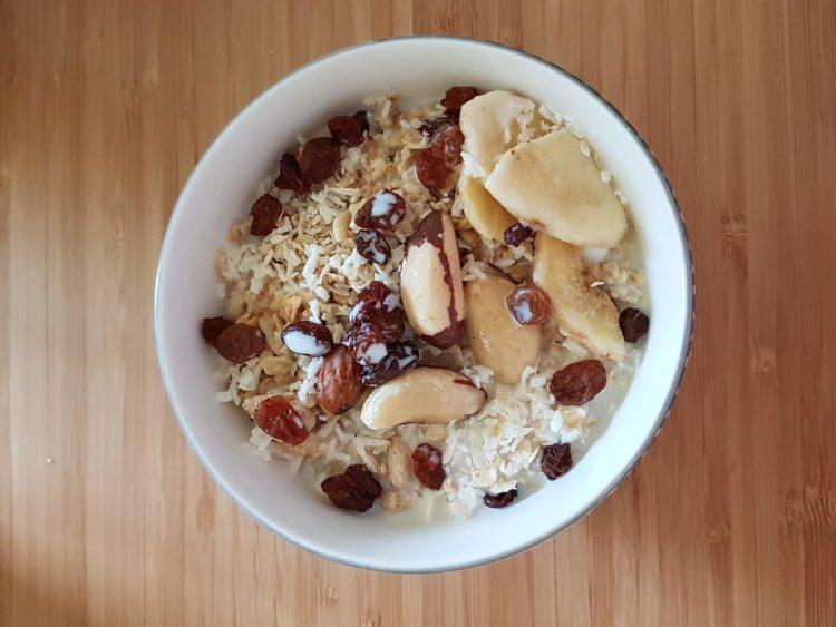 Un petit bol blanc avec du fromage blanc des flocons d'avoine des raisins secs de la banane de la noix de coco râpée et des noix du Brésil