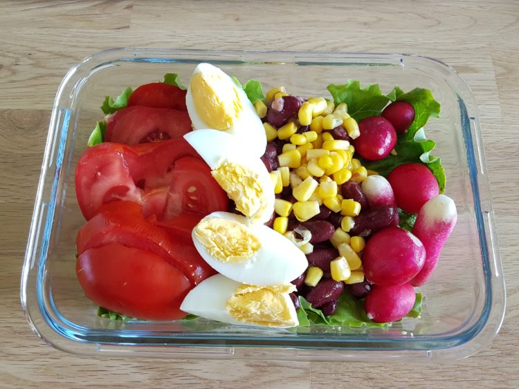 Lunchbox avec des oeufs durs, de la salade, des haricots rouges, du maïs, de la tomate et des radis