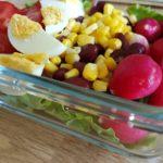 lunchbox contenant de la salade verte des œufs durs, des radis, des haricots rouges, du maïs et de la tomate