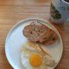 Assiette blanche contenant un œuf au plat et deux tranches de pain de campagne