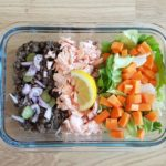 Plat transparent contenant des lentilles cuites du saumon cuit des crudités et une sauce vinaigrette à l'échalote