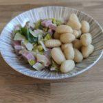 Une assiette creuse présentant des gnocchis et une fondue de poireau au jambon