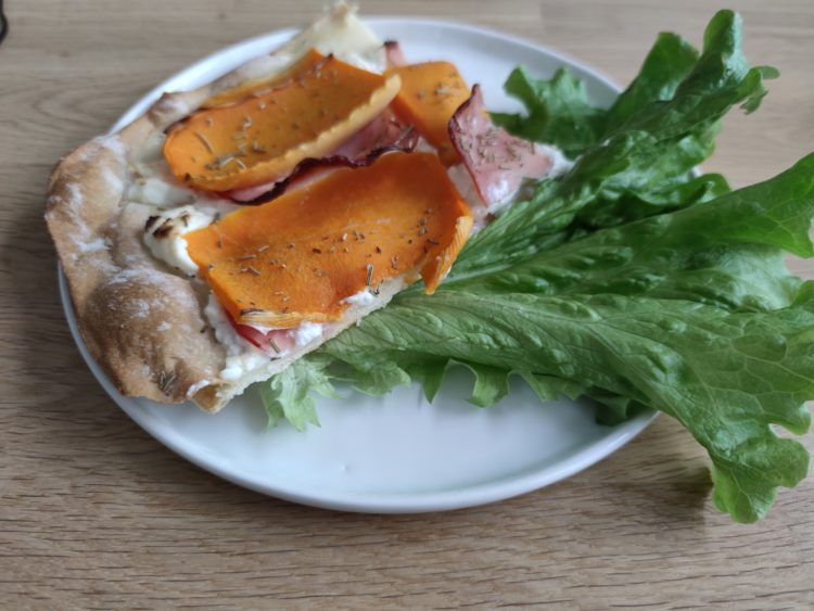 Part de tarte courge butternut présentée dans une assiette avec une feuille de salade