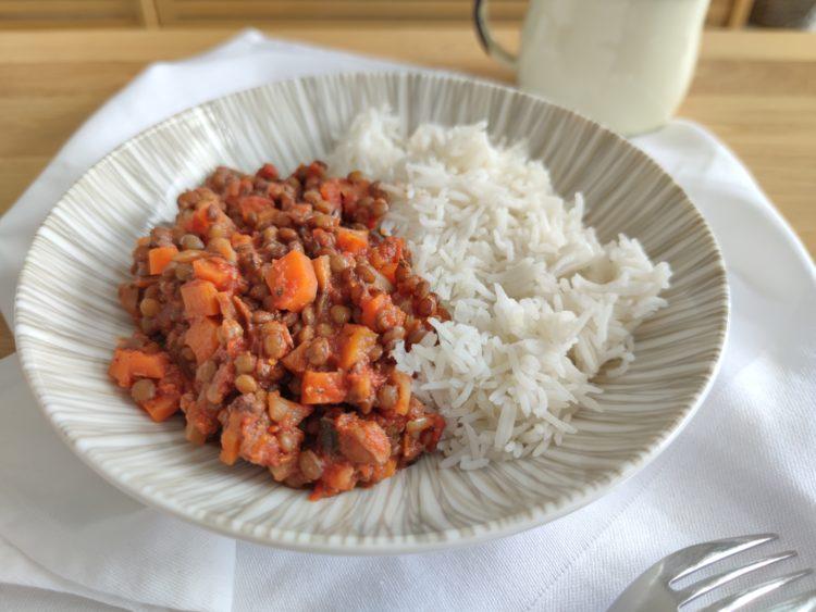 Lentilles blondes cuisinées à la bolognaise présentées dans une assiette creuse avec du riz basmati