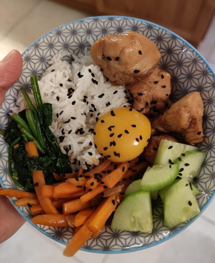 Bol avec un fond bleu et blanc contenant du riz, des carottes, du concombre, des épinards, du poulet, un œuf et des graines de sésame noir