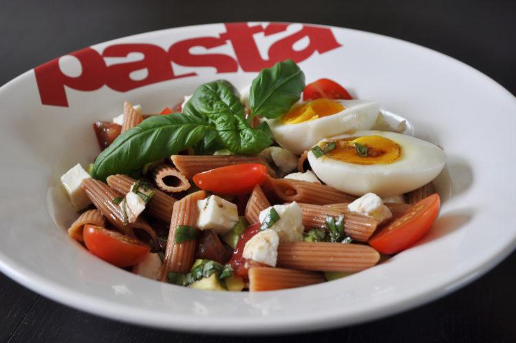 assiette blanche creuse de pâtes de lentilles corail avec œuf, tomates, basilic, avocat