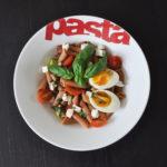 assiette blanche creuse contenant une salade de pâtes de lentilles corail avec œuf, tomates, basilic, avocat